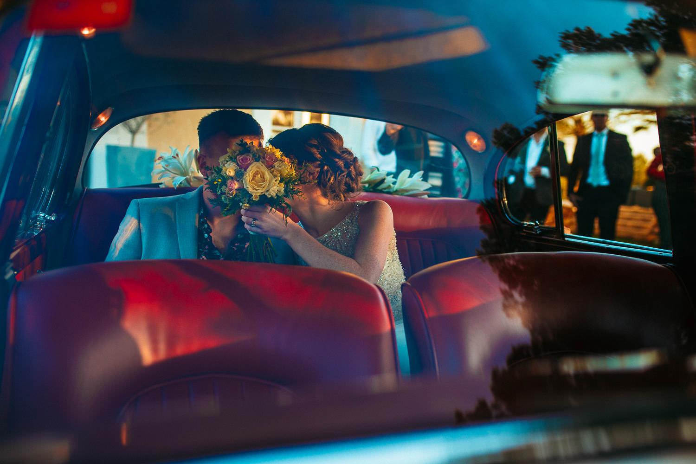 bride and groom hiding behind the bride's bouquet