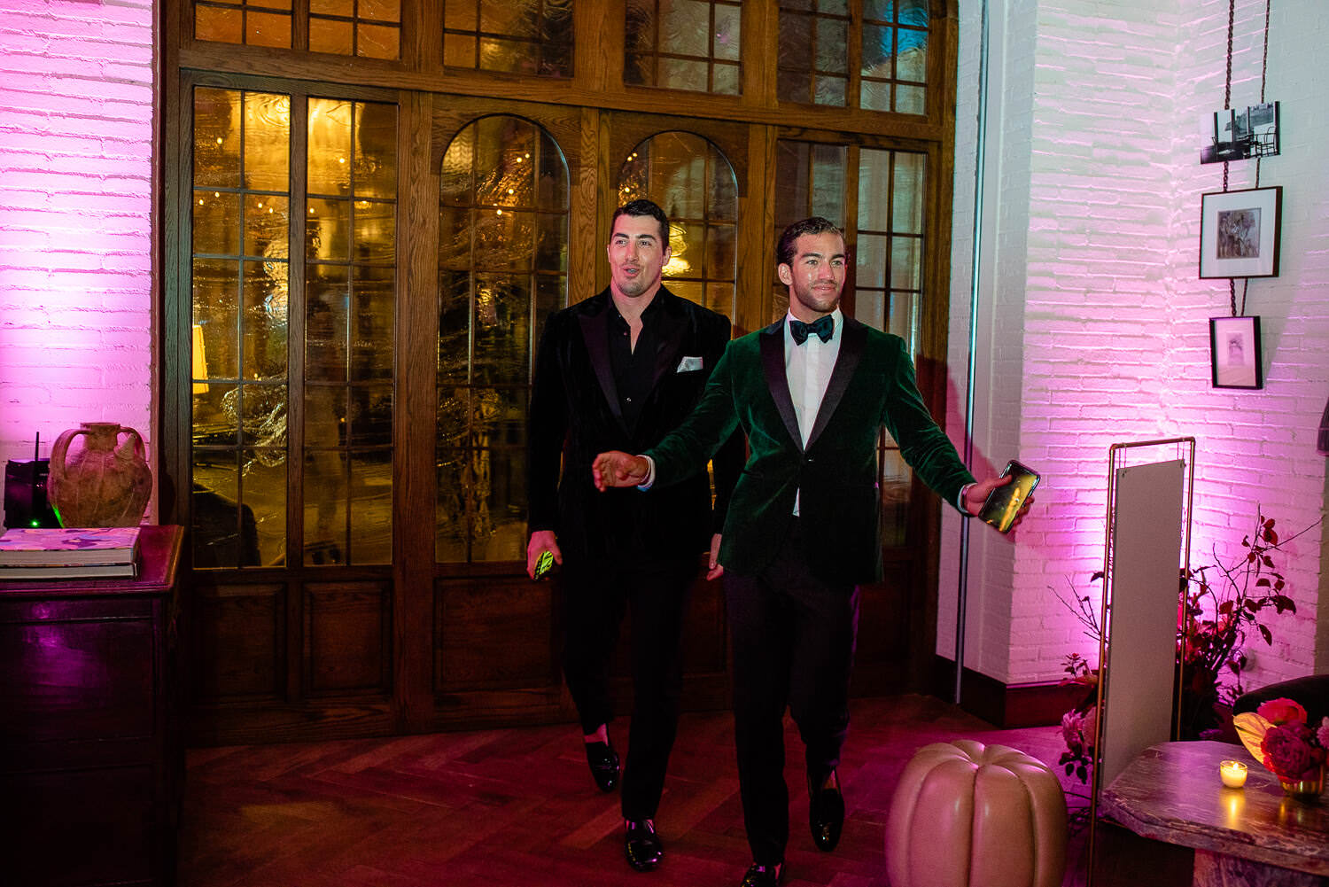 grooms newlyweds entering the dinner party on their same sex wedding at